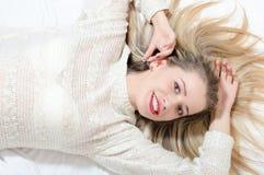 Schöne nette junge blonde Frau mit den roten Lippen, die auf dem Bett hat Spaß lachend liegen, Kameraporträtbild betrachtend Lizenzfreies Stockfoto