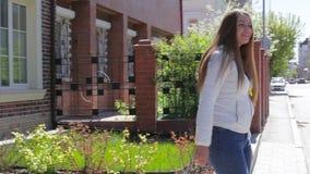 Schöne nette junge Frau geht zur Straße und zum Wellenartig bewegen heraus stock video