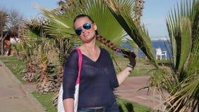 Schöne nette Mädchenstände nahe Palme genießt die Sonne stock video