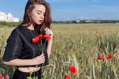 Schöne nette sexy junge Frau mit den vollen Lippen mit dem kurzen Haar auf einem Gebiet mit Mohnblume blüht in ihren Händen Stockbilder