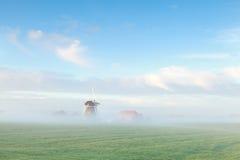 Schöne niederländische Windmühle im Morgennebel stockfotos