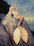 Schöne Nixe, die auf Felsen sitzt Stockfotos