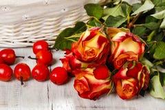 Schöne orange Rosen, roter Apfel- und weißerweidenkorb Stockfoto