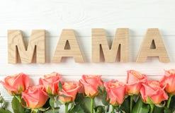 Schöne orange Rosen und Aufschrift Mutter auf weißem Hintergrund stockbilder