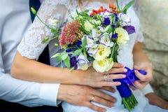 Schöne Paarbraut und -bräutigam mit einem Blumenstrauß, der auf Bank sitzt Lizenzfreie Stockfotografie