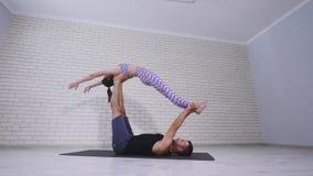 Schöne Paare übendes acro Yoga Junge Yogalehrerpraxis in einem Studio Zwei erfolgreiche junge Leute führen durch Lizenzfreie Stockfotografie