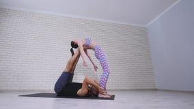 Schöne Paare übendes acro Yoga Junge Yogalehrerpraxis in einem Studio Zwei erfolgreiche junge Leute führen durch Stockbilder