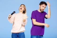 Schöne Paare über blauem Hintergrund Mädchen, das im Mikrofonmann didpleased singt Stockfoto