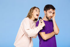 Schöne Paare über blauem Hintergrund Mädchen, das im Mikrofonmann didpleased singt Lizenzfreies Stockbild