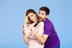 Schöne Paare über blauem Hintergrund Mann, der im Mikrofonmädchen didpleased singt Stockfoto