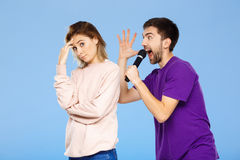Schöne Paare über blauem Hintergrund Mann, der im Mikrofonmädchen didpleased singt Stockfotos