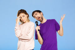 Schöne Paare über blauem Hintergrund Mann, der im Mikrofonmädchen didpleased singt Lizenzfreie Stockfotografie