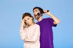Schöne Paare über blauem Hintergrund Mann, der im Mikrofonmädchen didpleased singt Lizenzfreies Stockfoto
