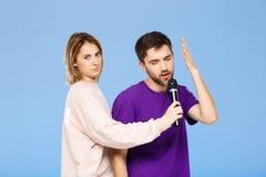 Schöne Paare über blauem Hintergrund Mann, der im Mikrofonmädchen didpleased singt Stockbilder