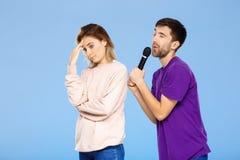 Schöne Paare über blauem Hintergrund Mann, der im Mikrofonmädchen didpleased singt Stockbild