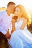 Schöne Paare auf dem Gebiet, Liebhabern oder Jungvermählten, die auf Sonnenuntergang mit perfektem Himmel aufwerfen Stockfoto