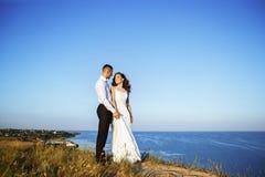 Schöne Paare auf dem Gebiet, Liebhabern oder Jungvermählten, die auf Sonnenuntergang mit perfektem Himmel aufwerfen Lizenzfreies Stockfoto