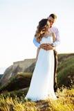 Schöne Paare auf dem Gebiet, Liebhabern oder Jungvermählten, die auf Sonnenuntergang mit perfektem Himmel aufwerfen Lizenzfreie Stockbilder