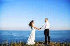 Schöne Paare auf dem Gebiet, Liebhabern oder Jungvermählten, die auf Sonnenuntergang mit perfektem Himmel aufwerfen Stockbilder