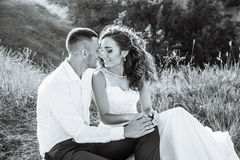 Schöne Paare auf dem Gebiet, Liebhabern oder Jungvermählten, die auf Sonnenuntergang mit perfektem Himmel aufwerfen Rebecca 6 Stockbild