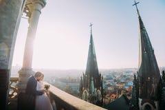 Schöne Paare, Braut und Bräutigam, die auf altem Balkon mit Spalte, Stadtbildhintergrund aufwirft stockfotografie