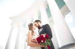 Schöne Paare, Braut und Bräutigam, die nahe großer weißer Spalte aufwirft stockfotografie