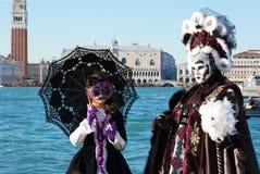 Schöne Paare in den bunten Kostümen und Masken, Ansicht über Marktplatz San Marco Stockfotos
