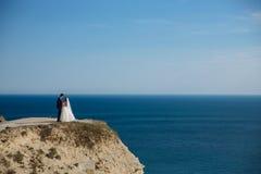 Schöne Paare des Jungvermähltens umarmend am Hochzeitstag auf Klippe mit Meerblick stockfotos