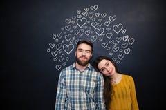 Schöne Paare, die über schwarzem Brett mit gezogenen Herzen stehen Stockfotografie