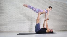 Schöne Paare, die acro Yoga im Studio tun Stockfoto