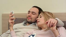 Schöne Paare, die auf dem Bett und Gebrauch Smartphone, Panoramafoto machend liegen stockbild