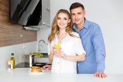 Schöne Paare, die auf Küche mit Pfannkuchen und frischem Saft stehen Lizenzfreie Stockfotos