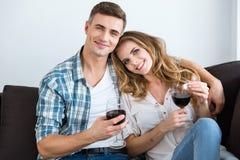 Schöne Paare, die auf Sofa und trinkendem Wein sitzen Stockfotos
