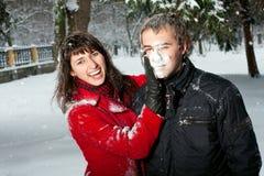 Schöne Paare, die im Schnee spielen Stockfoto