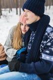 Schöne Paare, die im Winterwald auf Schnee sitzen Stockbilder