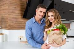 Schöne Paare, die Papierpaket des Lebensmittels halten Stockbild