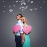 Schöne Paare, die rosa Herzen halten Stockbilder