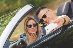 Schöne Paare, die Selbstporträt von ihrem Cabrioletauto in der Natur nehmen stockbilder
