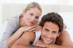 Schöne Paare, die sich auf ihrem Bett hinlegen Stockfotografie
