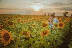 Schöne Paare, die Spaß auf den Sonnenblumengebieten haben Stockbilder