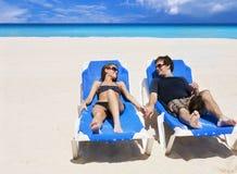 Schöne Paare, die Strandferien genießen Stockbilder