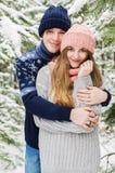 Schöne Paare, die unter schneebedeckten Tannenbäumen embacing sind Stockbild
