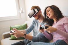 Schöne Paare, die Videospiele auf Konsole spielen lizenzfreie stockfotografie