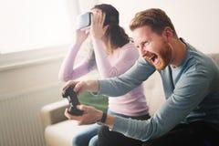 Schöne Paare, die Videospiele auf Konsole spielen stockbilder