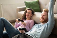 Schöne Paare, die Videospiele auf Konsole spielen stockbild