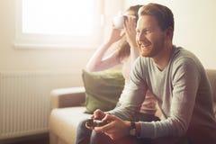 Schöne Paare, die Videospiele auf Konsole spielen stockfoto