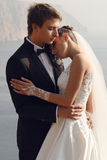 Schöne Paare herrliche Braut im Hochzeitskleid, das mit elegantem Bräutigam auf Seekosten aufwirft Lizenzfreie Stockfotografie