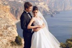 Schöne Paare herrliche Braut im Hochzeitskleid, das mit elegantem Bräutigam auf Seekosten aufwirft Lizenzfreie Stockfotos