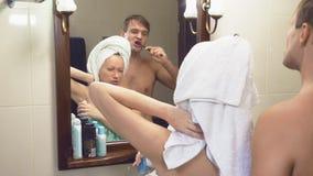 Schöne Paare, Mann und Frau, waschen sich zusammen im Badezimmer vor dem Spiegel 4k, Zeitlupe, der Ehemann stock footage