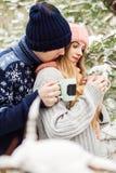 Schöne Paare mit heißem Tee in den Schalen im Wald Stockbild